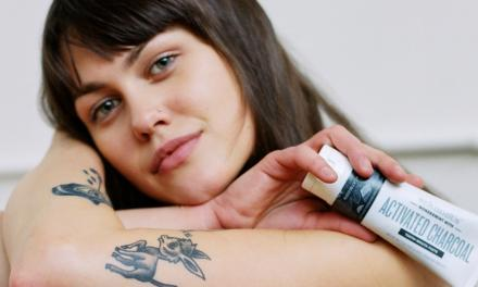 Woman holding Schmidt's activated charcoal toothpaste and looking into camera with white background